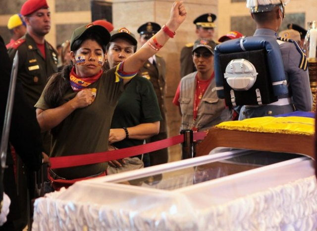 A supporter of late Venezuelan President Chavez gestures as she views his coffin during a wake at military academy in Caracas